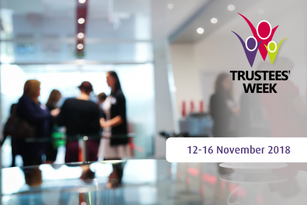 """A meeting room with people in the background. Has the Trustees' Week logo in the corner and a banner saying """"12-16 November 2018""""."""