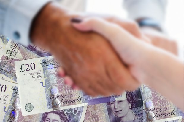 A photograph of two people shaking hands with lots of £20 notes in the background.
